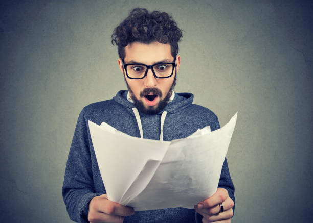 Excited man looking at papers in shock Handsome man in eyeglasses exploring documents and looking shocked with results. fee stock pictures, royalty-free photos & images
