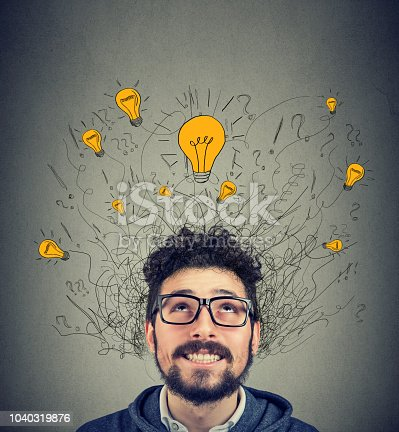 istock Excited man looking up at many ideas light bulbs above head 1040319876