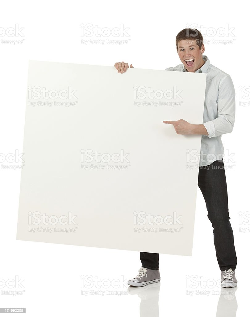 Excited man pointing at a placard royalty-free stock photo