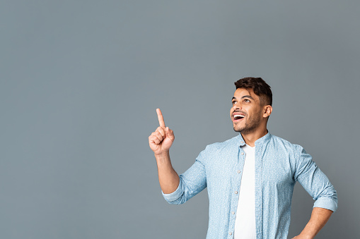 istock Excited Man Pointing Finger Upwards At Copyspace On Gray Background. 1165525334