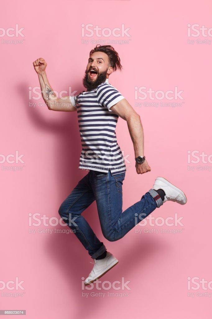 Hombre excitado posando en el salto en rosa - foto de stock