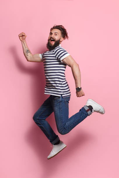Excited man posing in jump on pink stock photo