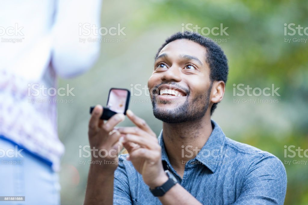 Excited man proposes to girlfriend stock photo