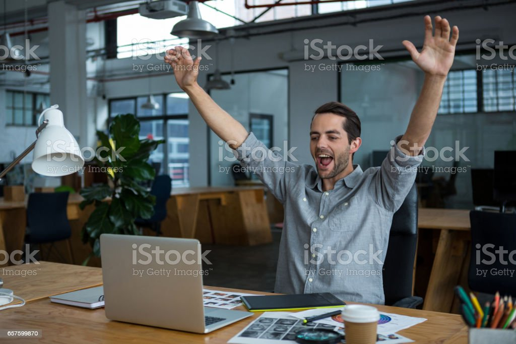 Excited man sitting with laptop at desk royalty-free stock photo