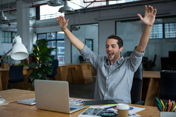 Excited man sitting with laptop at desk stock photo