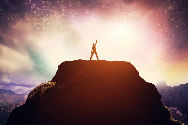 excited man standing on the peak of a mountain. - conquering adversity stock photos and pictures