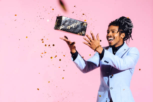Excited man throwing gift in the air amid falling gold confetti Excited man throwing gift in the air amid falling gold confetti amid stock pictures, royalty-free photos & images