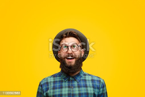 Amazed young hipster in shock looking up with surprise standing on bright yellow backdrop
