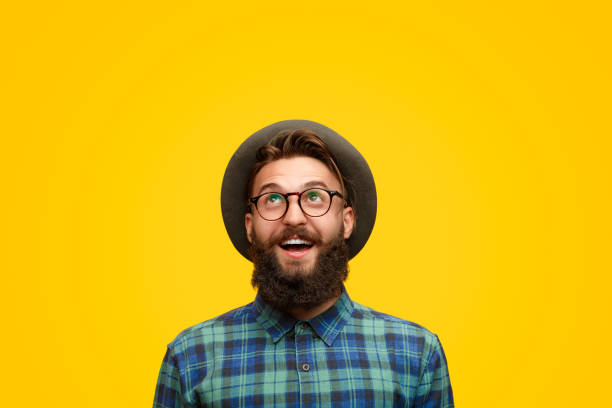 Excited man with beard looking up Amazed young hipster in shock looking up with surprise standing on bright yellow backdrop plaid shirt stock pictures, royalty-free photos & images