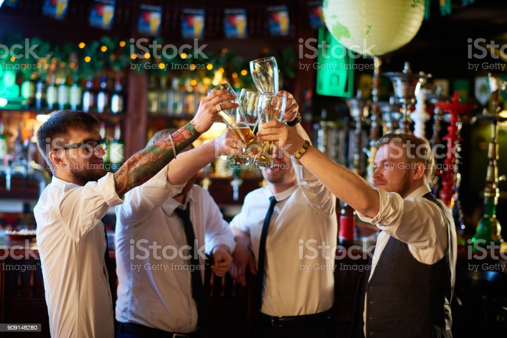 Excited managers celebrating success at pub stock photo