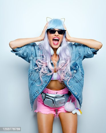 Portrait of beautiful blue and pink log hair young woman wearing oversized jeans jacket, cat ears headband, sunglasses and pink shorts. Studio shot.