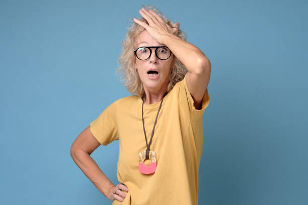 Excited mature blonde woman in glasses holding her head stock photo