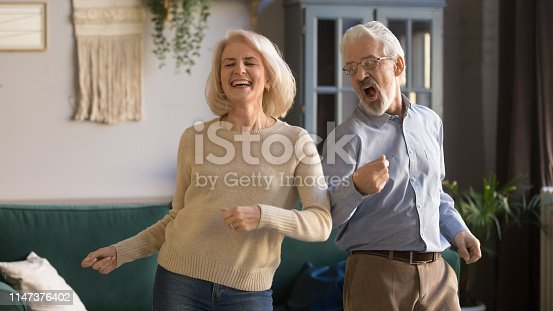 Excited mature couple, laughing grey haired man and woman having fun, dancing to favorite music at home in living room, middle aged wife and husband spending weekend together, funny activity