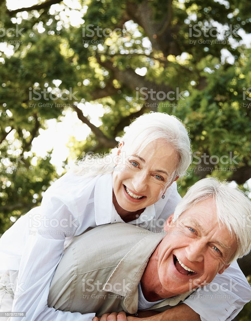 Excited mature man giving piggyback to his wife royalty-free stock photo