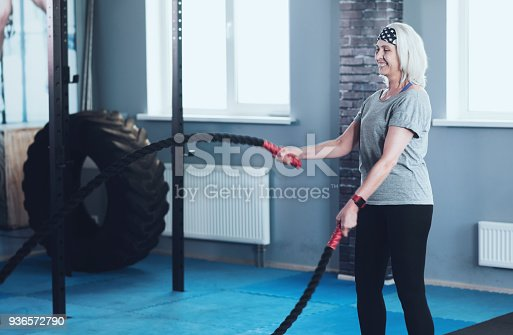 936573360 istock photo Excited mature woman exercising with battle ropes at gym 936572790