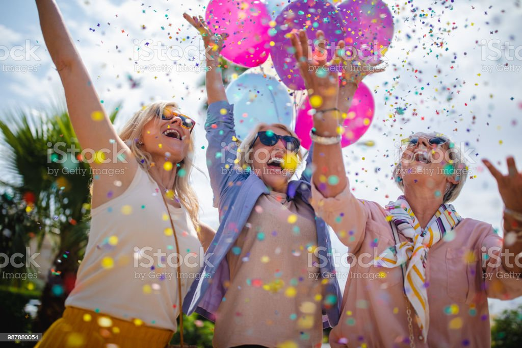 Excited mature women celebrating with colorful confetti and balloons outdoors stock photo