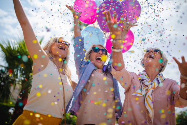 excited mature women celebrating with colorful confetti and balloons outdoors - mulher balões imagens e fotografias de stock
