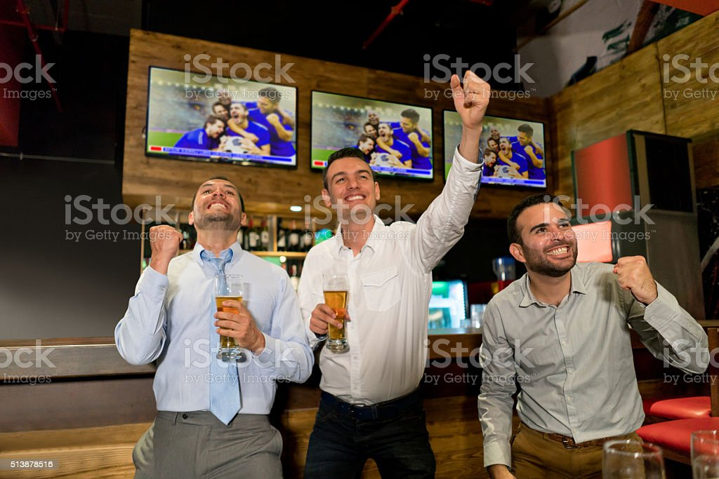 Excited men watching football at the bar stock photo
