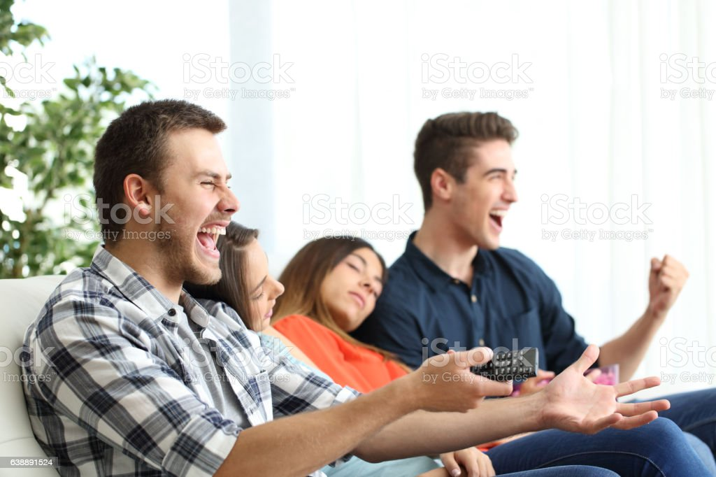 Excited men watching tv and bored girlfriends stock photo