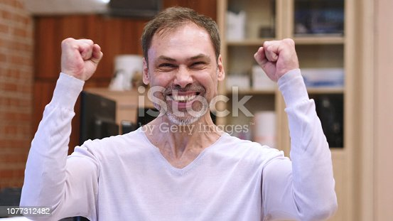 888751614 istock photo Excited Middle Age Man Celebrating Success in Office 1077312482
