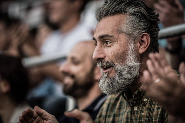 excited middle-aged man with gray hair and beard - soccer supporter portrait imagens e fotografias de stock