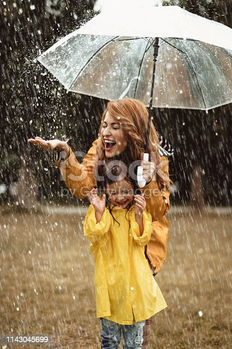 Full length of happy mother standing under umbrella with small girl. She is stretching hand trying to catch water drops with closed eyes in delight