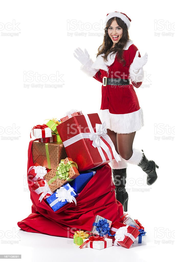 Excited Mrs. Claus and bag full of gifts. stock photo