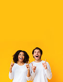 istock Excited multiracial couple looking and pointing upwards at copy space 1198238751