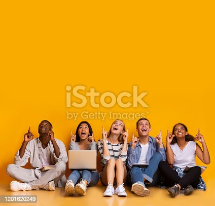 istock Excited multiracial students pointing up at copy space 1201620249