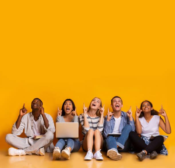 コピースペースを指し示す興奮した多人種の学生 - people of color ストックフォトと画像