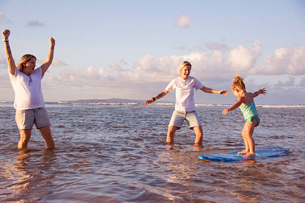 Excited mum's teaching daughter to surf stock photo
