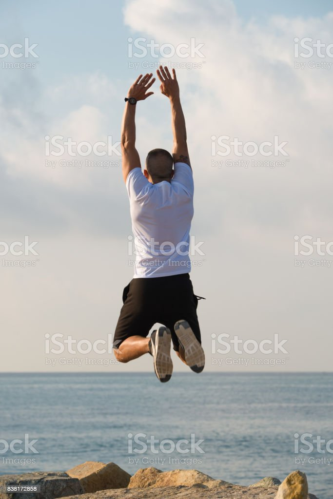 Excited muscled man with raised arms in mid-air stock photo