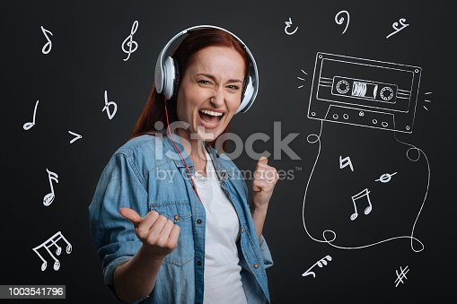 1003539592istockphoto Excited musician wearing headphones and listening to her new song 1003541796