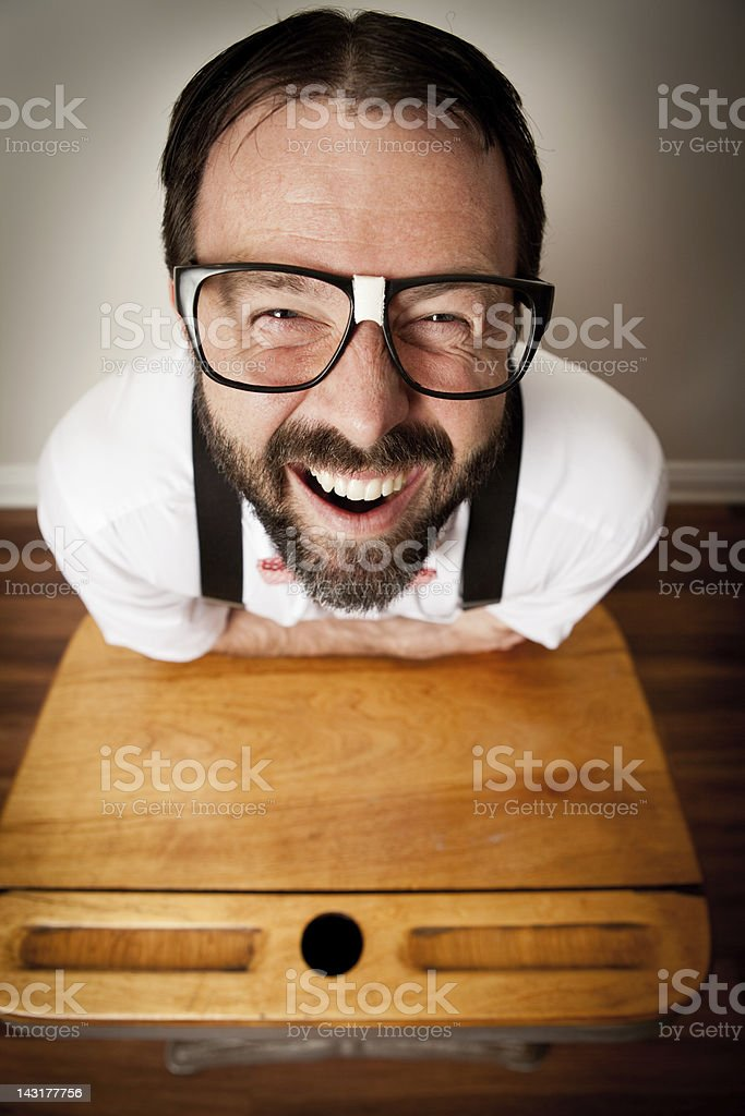 Excited Nerd Guy Sitting at Old School Desk royalty-free stock photo