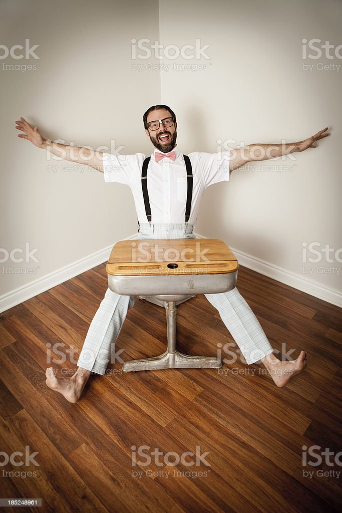 Excited Nerd Guy Sitting in Corner at Old School Desk royalty-free stock photo