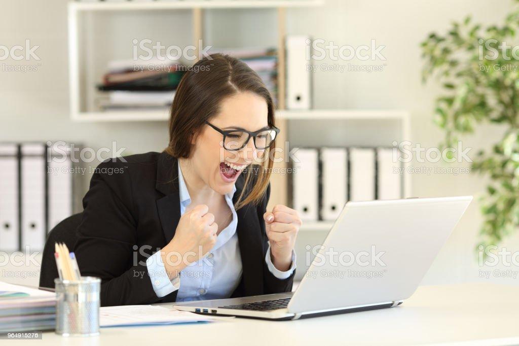 興奮的辦公室工作人員在筆記本電腦上閱讀線上新聞 - 免版稅互聯網圖庫照片