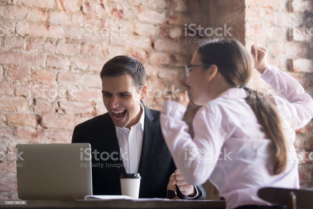 Excited Office Workers Screaming With Joy Looking At Laptop Screen