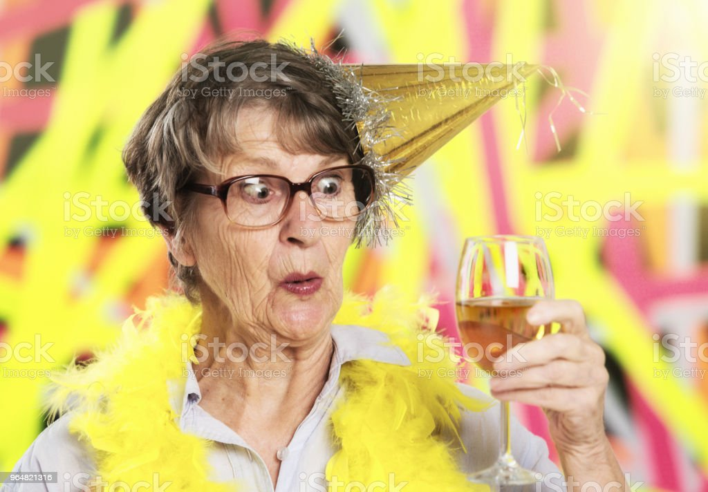 Excited old woman at party eyes glass of champagne eagerly royalty-free stock photo