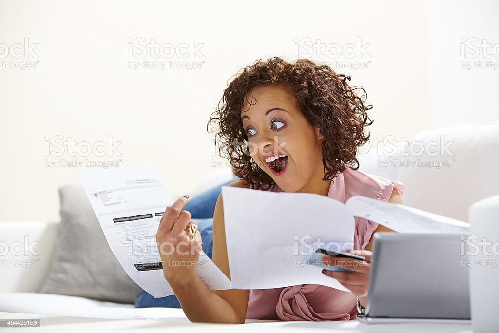 Excited oung lady looking at her credit card bill royalty-free stock photo