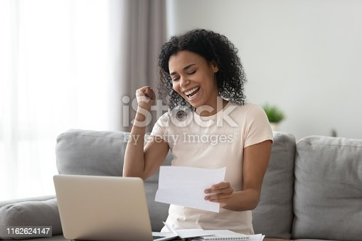 istock Excited overjoyed black girl student read good news in letter 1162624147