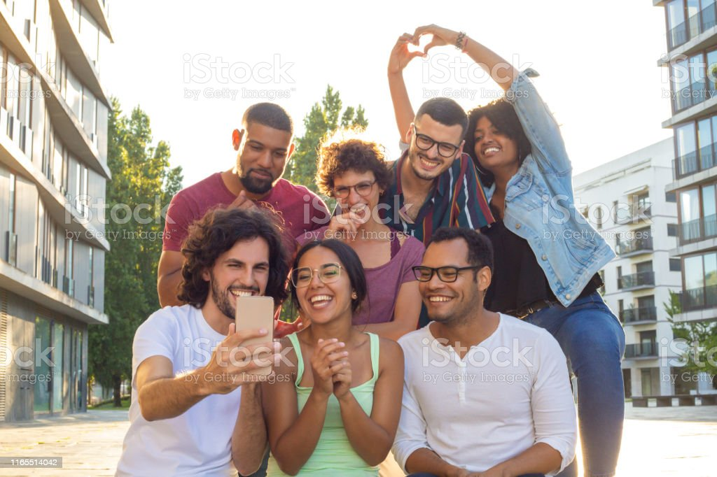 Excited overjoyed multiethnic people taking group selfie outside. Mix...