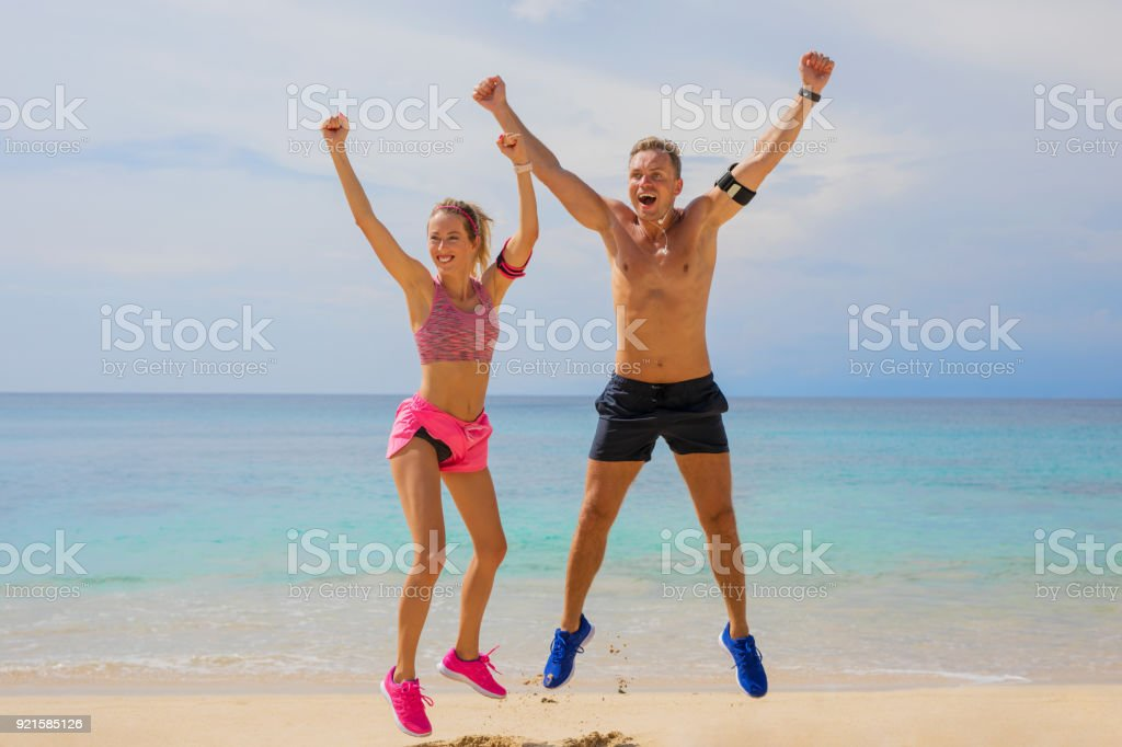 Excited people after workout on the beach, two Caucasian ethnicity...