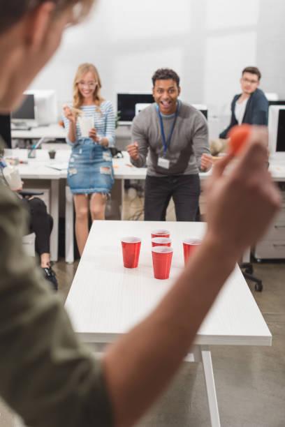 opgewonden mensen bier pong spelen op moderne kantoor na het werk - beirut stockfoto's en -beelden
