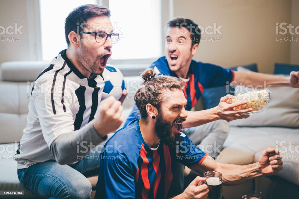 Happy men wearing soccer uniforms and watching game on TV