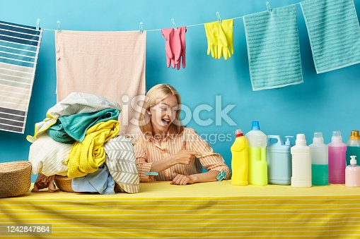 excited positive girl indicates at bottles of washing soap. Make your laundry easy.goods, business, best detergent for housewife.advertisement, advert, ad concept