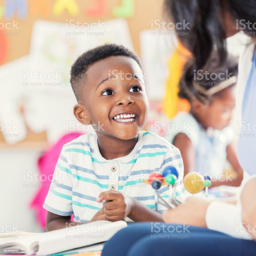 An excited little boy sits at a table in his preschool classroom with...