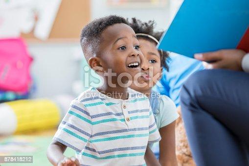 istock Excited preschool boy enjoying story time 878418212