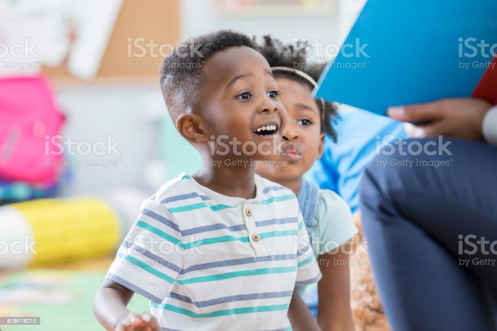 Excited preschool boy enjoying story time stock photo