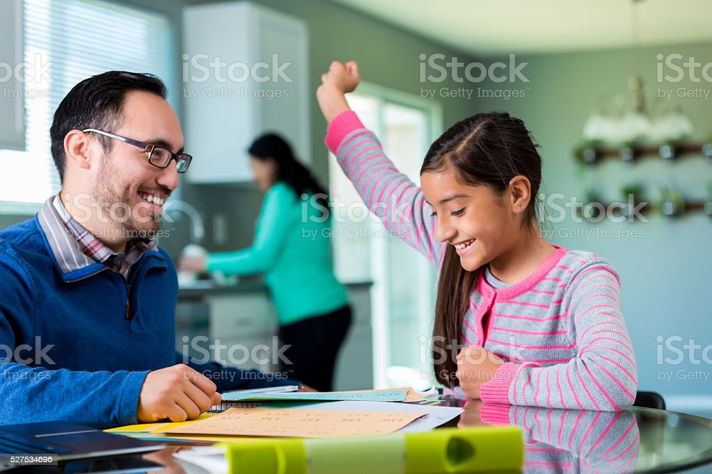 Excited pre-teen girl celebrates after finishing project stock photo