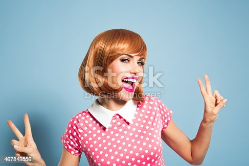 Portrait of happy red hair young woman wearing polka dot pink dress. Standing against blue backgorund, gesturing vicory v sign and laughing at camera. Studio shot, one person, headshot.